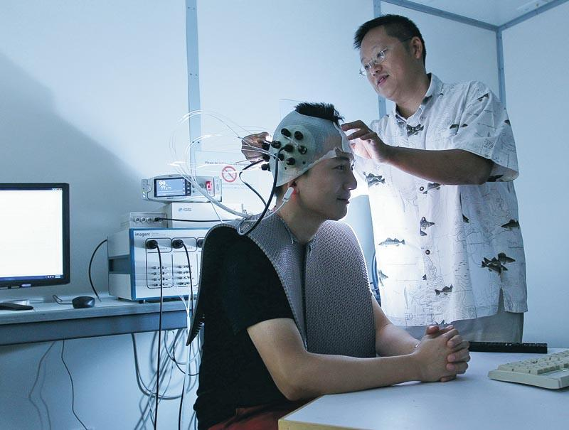 生物醫學工程結合了生命與科技,圖為蘇孝宇教授 (圖右) 利用近紅外光譜系統來量度大腦反應。