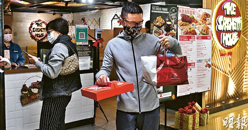 昨晚冬至,惟在限聚令禁下午6時後堂食下,食肆只能透過外賣幫補生意。圖為太古城商場,市民前往餐廳領取外賣。(林靄怡攝)