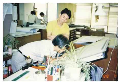 圖為1988年建築署技術主任在金鐘道政府合署辦公室工作情况,當年要在繪圖板繪畫及檢視圖則。(建築署提供)