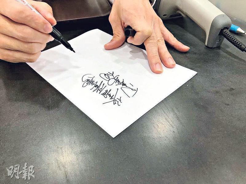當舖字——長江大押經理陳先生示範如何寫出只有行內人才懂的當舖字,這是入行時必須學會的技能。紙張上的字是「低金鑲石戒指一隻」和「銅殼手表一個」,你又能辨認出來嗎?(鄧捷攝)