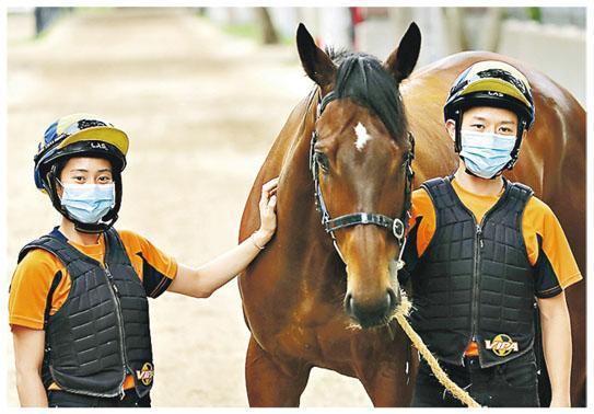 馬會賽事見習學員黃寶妮(左)話最初入學時要喺學校寄宿,唔太習慣離開屋企,但學員互相鼓勵照顧,好快就克服咗。另一學員黎彥麟(右)曾去比利時學馬術,期望日後做到見習騎師。(馬會提供)