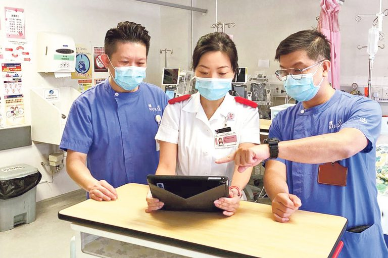 護理工作講求團隊合作, V i v i a n ( 中) 跟護理人員一 起討論病人的情况, 為病人 提供最合適的護理方案。
