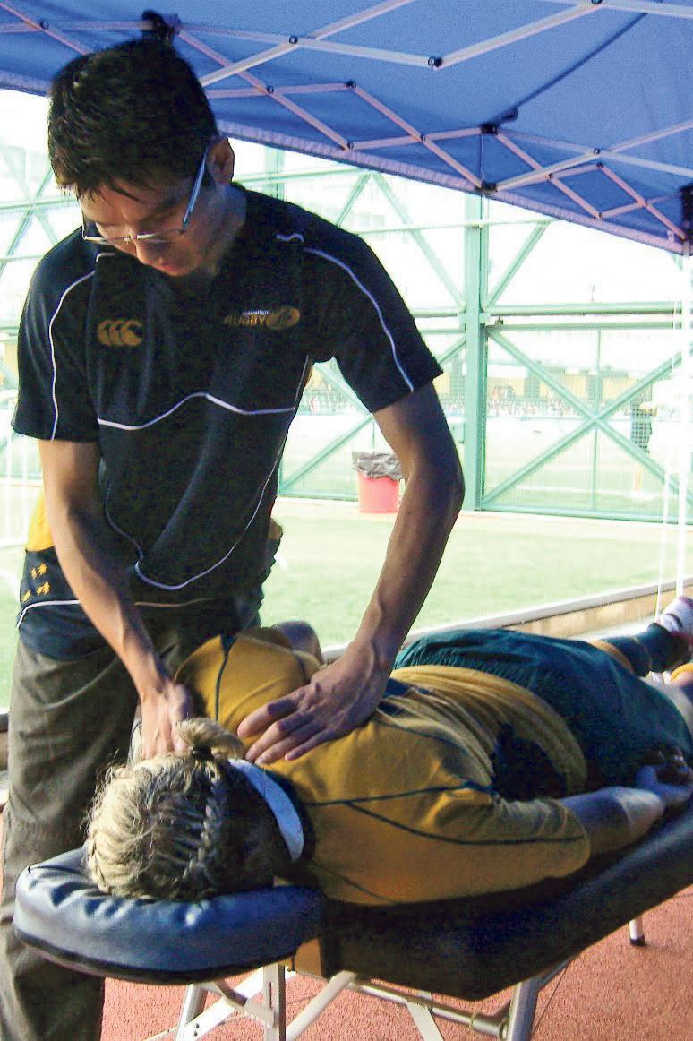 Elton(站立者)為運動員拉 筋、按摩、處理傷口等,使他 們能以最佳狀態參與比賽。