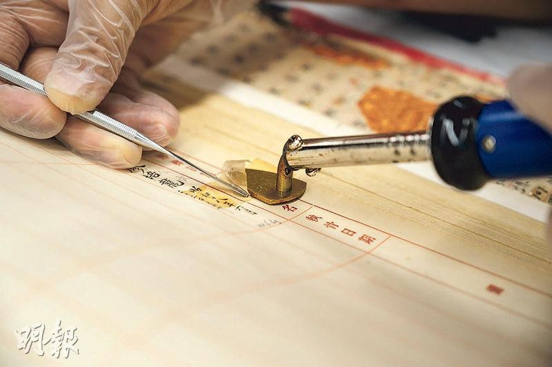 去除膠紙——文物復修專家方惠燕先以小熨斗把膠紙熨熱熨軟,再用抹刀剷走膠紙。不同類型的膠紙,硬度和黏性各異,需配以不同溶劑及漿水處理。(蘇智鑫攝)